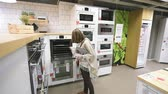 globalizace : PARIS, FRANCE - CIRCA 2018: Multiple contemporary IKEA furniture store with woman customer browsing through diverse furniture, decoration warehouse goods oven stove selection in kitchen