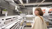 sala de exposição : PARIS, FRANCE - CIRCA 2018: Multiple contemporary IKEA furniture store with woman customer browsing through diverse furniture, decoration warehouse goods buy bathroom accesories Stock Footage