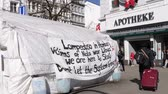immigrant : HAMBURG, GERMANY - CIRCA 2018: Lampedusa migrants in Hamburg center - migrants tent with inscriptions about war in Libya, NATO presence and Lampedusa Drug Store Pharmacy Apotheke
