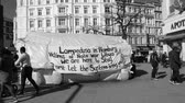 immigrant : HAMBURG, GERMANY - CIRCA 2018: Black and white slow motion scene with pedestrians walking in front of migrants tent with inscriptions about war in Libya, NATO presence and Lampedusa island