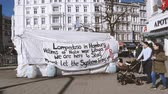 working parents : HAMBURG, GERMANY - CIRCA 2018: Slow motion scene with pedestrians pushing trolley walking in front of migrants tent with inscriptions about war in Libya, NATO presence and Lampedusa