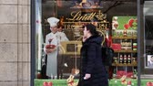 bakery shop : HAMBURG, GERMANY - CIRCA 2018: Lindt & Sprungli chocolate sweets store in central Hamburg on the Spitalerstrasse with people customers entering the sweets food store with Rodolphe Lindt portrait Stock Footage