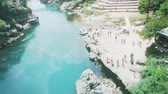 ЮНЕСКО : MOSTAR, BOSNIA AND HERZEGOVINA - CIRCA 2018: View from standstill drone camera of tourist crowd admiring UNESCO heritage Mostar Stari most bridge over blue Neretva river on a hot summer day Стоковые видеозаписи