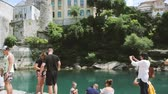 воспоминания : MOSTAR, BOSNIA AND HERZEGOVINA - CIRCA 2018: Hundreds of tourists admiring and taking photos of UNESCO heritage Mostar Stari most bridge with horizontal panning on turquoise Neretva river on a hot summer day
