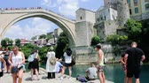 kulturní : MOSTAR, BOSNIA AND HERZEGOVINA - CIRCA 2018: Pan over large crowd of people admiring and taking photos of UNESCO heritage Mostar Stari most bridge with horizontal panning on Neretva river on a hot summer day Dostupné videozáznamy