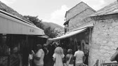 documentary : MOSTAR, BOSNIA AND HERZEGOVINA - CIRCA 2018: View from Mostar Stari most bridge of tourists walking up and down busy bazar street in the Mostar old city on a hot summer day - black and white
