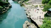 most : MOSTAR, BOSNIA AND HERZEGOVINA - CIRCA 2018: View from standstill drone camera of tourist crowd admiring UNESCO heritage Mostar Stari most bridge over blue Neretva river on a hot summer day Stock Footage