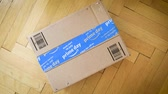 parke : PARIS, FRANCE - JUL 12: Rotation over Amazon Prime Day cardboard parcel on wooden parquet floor with special blue scotch tape for the Prime Day offering a day of deals, discounts, and great shopping Stok Video