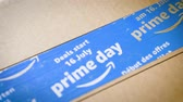 discounts : PARIS, FRANCE - JUL 12: Zoom-out from Amazon Prime Day cardboard parcel on wooden parquet floor with special blue scotch tape for the Prime Day offering a day of deals, discounts, and great shopping