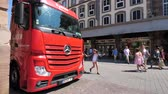 грузоперевозки : STRASBOURG, FRANCE - JUL 16, 2018: Side view of new powerful red Mercedes-Benz Actros truck parked on city street near shopping stores with pedestrians walking nearby French city street Стоковые видеозаписи