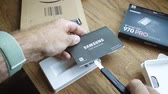 razzia : PARIS, FRANCE - CIRCA 2018: Man hand unboxing new Samsung 870 Pro NVME PCIE SSD hard drive disk with high read and write speed - reading the instruction installation manual