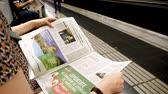 presidente : BARCELONA - JUNE 1 2018: Woman reading in Barcelona Metro station the La Vanguardia newspaper slow motion footage with commuters in background on platform Spanish politics reading about