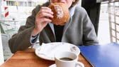 au : Woman eating delicious croissant pain au chocolate in French cafe early in the morning drinking freshly roasted coffee - Parisian lifestyle Stock Footage
