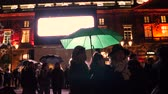 inauguration : STRASBOURG, FRANCE - NOV 23, 2017: Women under green umbrella at Strasbourg Christmas Market in France, the oldest in Europe inauguration ceremony in Place Kleber at night