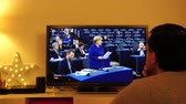 parlament : STRASBOURG, FRANCE - NOV 13, 2018: Man watching Phoenix German TV broadcasting live German Chancellor Angela Merkel speech about future of Europe with members of European Parliament
