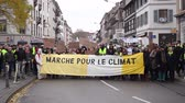 protester : STRASBOURG, FRANCE - DEC 8, 2018: Side view of large crowd of people marching in Central Strasbourg at the nationwide protest Marche Pour Le Climate with large yellow palcard