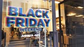 weekdays : PARIS, FRANCE - CIRCA 2018: Black Friday weekend sale sign in the showcase store window of a modern shopping facade on a pedestrian street with reflection of customers people Stock Footage