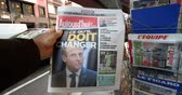 newspaper stack : PARIS, FRANCE - DEC 10, 2018: Newspaper stand kiosk stand selling press with man buying Aujourdhui Today newspaper featuring Emmanuel Macron on the front page