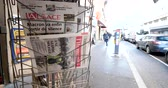newspaper stack : PARIS, FRANCE - DEC 10, 2018: Newspaper stand kiosk stand selling press with multiple newspaper featuring news about events in France And pedestrian silhouettes walking calmly in background Stock Footage