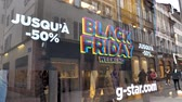 weekdays : PARIS, FRANCE - CIRCA 2018: Black Friday sale sign in the showcase store window of a modern shopping facade on a pedestrian street with reflection of customers people