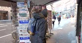 newspaper stack : PARIS, FRANCE - DEC 10, 2018: Rear view of adult man at newspaper stand kiosk stand selling press with multiple French newspapers, lOpinion, Express, Le monde, Le figaro, Monde Economique, Les Echos, La Tribune