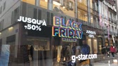 farra : PARIS, FRANCE - CIRCA 2018: Black Friday sale sign in the showcase store window of a modern shopping facade on a pedestrian street with reflection of customers people