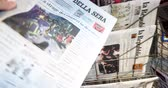 newspaper stack : PARIS, FRANCE - DEC 10, 2018: Newspaper stand kiosk stand selling Italian press Corriere Della Sera with title on cover about Six dead and dozens hurt in nightclub stampede in Italy Stock Footage