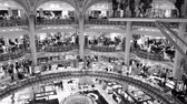juwelier : PARIS, FRANCE - CIRCA 2019: Black and white footage aerial drone pan over the Art Nouveau interior of luxury fashionable interior of Galeries Lafayette with thousands of customers shopping for world known brand Stockvideo