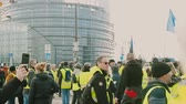 strike : STRASBOURG, FRANCE - FEB 02, 2018: Police and protestors in front of European Parliament - people demonstrating walking during protest of Gilets Jaunes Yellow Vest anti-government demonstrations Stock Footage
