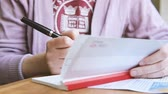 сумма : Handheld video of woman preparing to fill a banking cheque check writingwith luxury fountain pen the requested data in the luxury first class checkbook