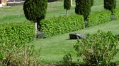 hortênsia : View from the street of luxury green garden with working in silence auto mower an mobile smart home controlled autonomous mower