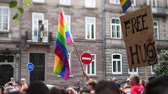 sexualität : Tilt-shift defocused crowd waving rainbow flags at annual FestiGays pride gays and lesbians parade marching French streets dancing fun party atmosphere Free hugs placard Videos