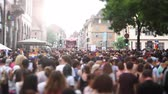 lésbica : STRASBOURG, FRANCE - CIRCA 2018: Cinematic flare over large crowd of people following gay pride truck at annual FestiGays pride gays and lesbians parade marching French streets dancing fun party atmosphere