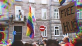 gays : Distorted RGB displacement tilt-shift lens over large crowd of people waving rainbow flags at annual FestiGays pride gays and lesbians parade marching French streets dancing fun party atmosphere
