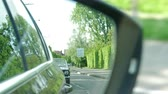 путь : NICE, FRANCE - CIRCA 2019: Side view car mirror reflection of two-lane road in city with Ford Mustang convertible car following - scene to be used in movies, stories and other editorial needs