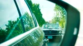 gázló : NICE, FRANCE - CIRCA 2019: Cinematic view through rear-view car mirror of two Ford Mustang convertible cars in city following behind - scene to be used in movies, stories and other editorial needs