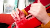 com cordas : Close-up of elegant female hands wearing red dress playing red small mandolin guitar