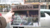buy press : Paris, France - Mar 15, 2019: Man hand holding against French city background Les Echos newspaper featuring Emmanuel macron President and Grand Debat news Great Debate - slow motion Stock Footage