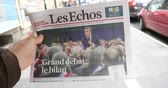 buy press : Paris, France - Mar 15, 2019: Man hand holding against French city background Les Echos newspaper featuring Emmanuel macron President and Grand Debat news Great Debate