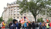 válság : Strasbourg, France - Sep 12, 2017: ESCA luxury building in central Strasbourg and protesters with CGT red flags at political march during a French Nationwide day of protest