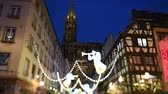 aziz : Strasbourg, France - Circa 2018: Tilt-shift lens over Strasbourg annual Christmas winter market with Notre-Dame cathedral view from Rue Merciere with angels light decorations over timbered houses