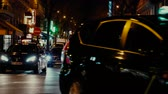 parisiense : Paris, France - Circa 2019: Cinematic color over typical French street in Paris with cars taxi commuters pedestrians at night commuting going home, restaurants sightseeing 4k UHD