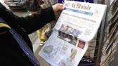 mei : Paris, France - 29 Mar 2019: POV newspaper stand kiosk selling press with senior male hand buying latest French Le Monde featuring Theresa May Brexit news on front cover