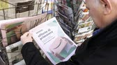 pov : Paris, France - 29 Mar 2019: Newspaper stand kiosk selling press with senior male hand buying latest Italian press featuring Amazon Oferta di Primavera spring offer on front cover Stock Footage