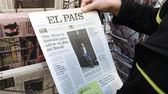 el : Paris, France - 29 Mar 2019: Newspaper stand kiosk selling press with senior curious male hand buying latest Spanish El Pais featuring Brexit news on front cover Stock mozgókép