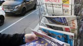 el : Paris, France - 29 Mar 2019: Newspaper stand kiosk selling press with senior male hand buying latest Quotidien Present featuring  European Elections on front cover with preferred racial election