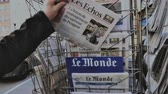 el : Paris, France - 29 Mar 2019: Newspaper stand kiosk selling press with senior male hand buying latest economical Les Echo featuring news about Peugeot car maker on front cover VHS vintage tape Stock mozgókép