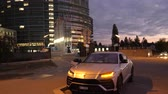 технология : Strasbourg, France - Circa 2019: Couple traveling in luxury Lamborghini Urus SUV taking photos of the European Parliament building at night in Strasbourg with al EU waving flags in background