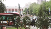 concertgebouw : Baku, Azerbaijan - Circa 2019: Heydar Aliyev Palace with saluting statue in memory of Azerbaijani President Heydar Aliyev with people exits red public transportation bus slow motion