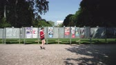 oslava : Strasbourg, France - May 23, 2019: Posters in green sunny park for 2019 European Parliament election featuring French politicians and female runner in front checking phone - slow motion